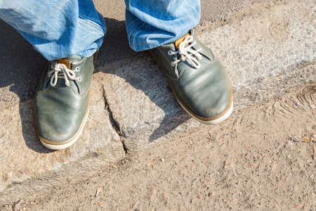 young man feet in sneakers on cobbled road