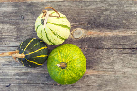 Autumn pumpkins with leaves on wooden board with shallow depth of field