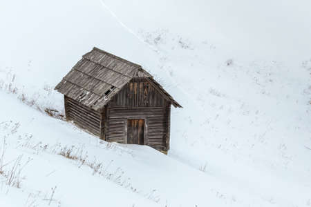 Small lonely house in the snowy mountains