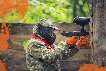 Paintball speler in beschermende uniforme en masker met een pistool in het voorhoesje Stockfoto