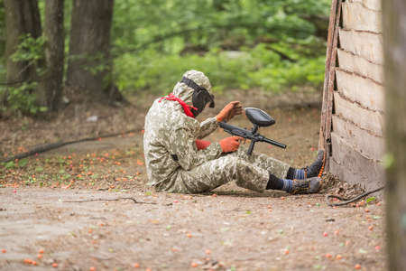 Paintball player in protective uniform and mask aiming gun in the forrest cover