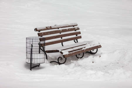 single bench covered with snow in winter park