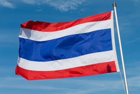 which: Thailand flag with blue sky in background. flag of Thailand