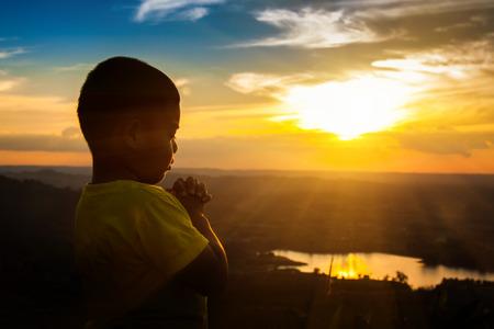 Un garçon qui prie sur la montagne, Dieu merci. Banque d'images - 71714972