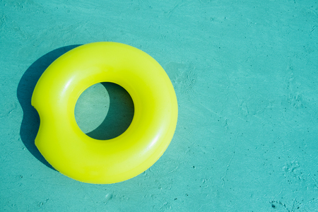 Yellow rubber ring on the beach in pastel style
