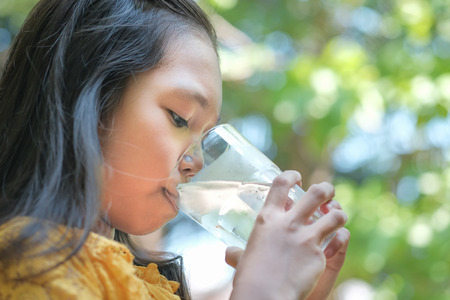 The girl is drinking cold water from the glass.