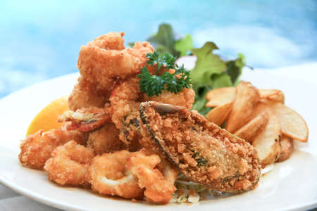 Deep-fried flour coated seafood with tartar sauce and home-cut fries photo