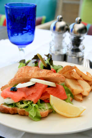 Big half moon stuffed croissant sandwich with smoked salmon with salad and home-cut fries photo