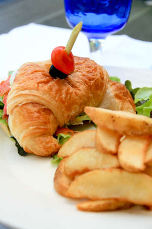 Big half moon stuffed croissant sandwich with smoked salmon with salad and home-cut fries - 1 photo
