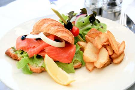 Deli: Big half moon stuffed croissant sandwich with smoked salmon, salad and home-cut fries Stock Photo
