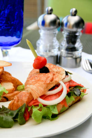 Big half moon stuffed croissant sandwich with smoked salmon, salad and home-cut fries. photo