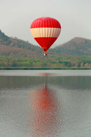 Red and White Hot Air Balloon rise up from the water photo