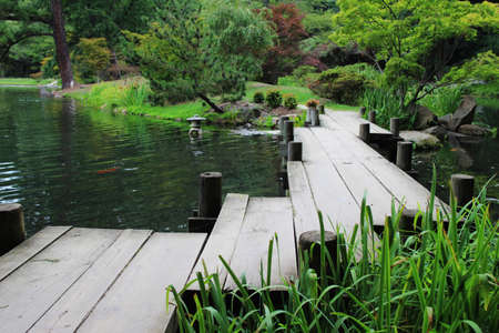 ponte giapponese: A wooden zig-zag bridge over a pond in a Japanese garden