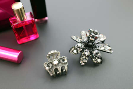 Close up of crystal black hair clips and feminine cosmetics on black background