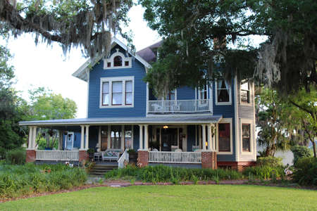 An old Southern-style house with a cozy front porch surrounded by live oak trees draped with Spanish moss, Amelia Island, Florida, USA