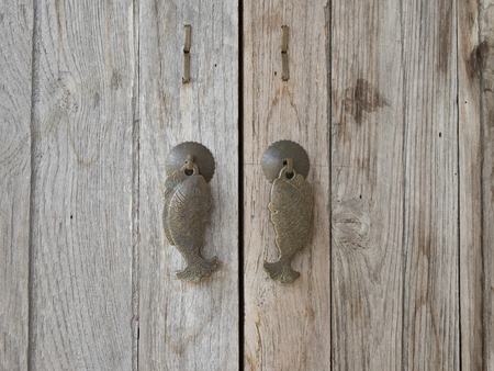 Fish door handle on the wood.