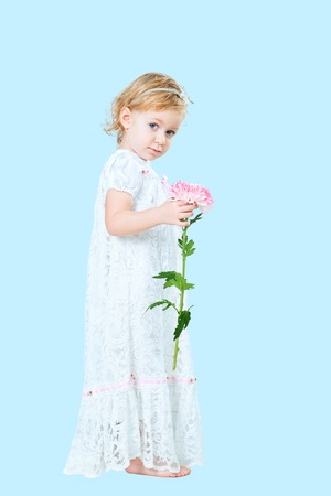 portrait of pretty girl wearing traditional laced dress for first communion isolated on blue background photo