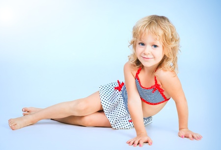 adorable smiling playful girl 4 years old lying on blue studio background