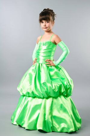 cute little girl posing on studio neutral background in gorgeous green gown photo