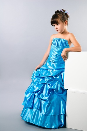 party dress: a cute girl posing in a prom dress in studio