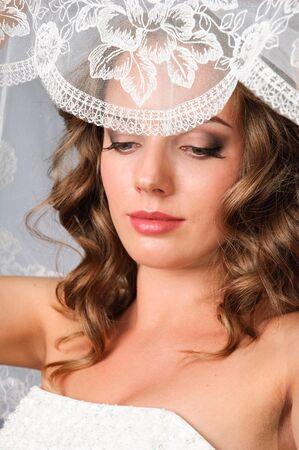 closeup portrait of beautiful bride opening a veil photo