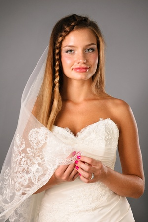 beautiful quiet young bride wearing wedding outfit on studio neutral background photo