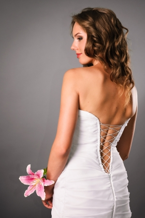side pose: beautiful bride with flower back view in studio