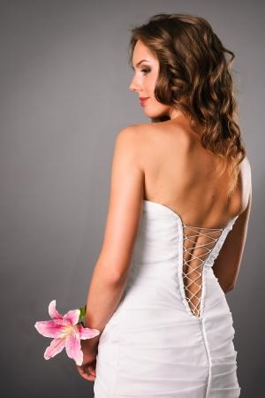 mujeres de espalda: hermosa novia con flor vista en estudio posterior