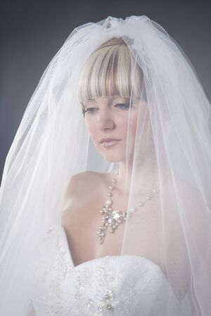 closeup portrait of romantic bride in the veil in studio photo