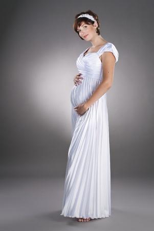 embarazada feliz: hermosa novia embarazada con un vestido de boda sobre un fondo neutro estudio