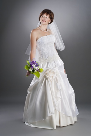 happy pregnant bride wearing wedding gown on studio neutral background photo