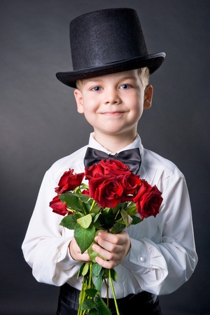 flowers boy: handsome boy wearing classic suit with flowers in hands Stock Photo