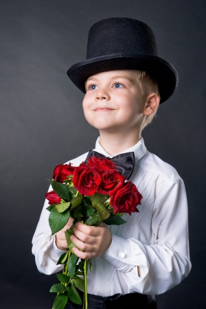 handsome boy wearing classic suit with flowers in hands photo