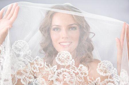 portrait of beautiful bride under veil on neutral background photo