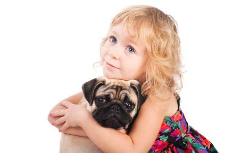 animalitos tiernos: Aislado retrato de niña bonita abrazando perro pug Foto de archivo