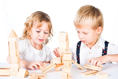 developing: Two kids playing with wooden blocks indoor on white background