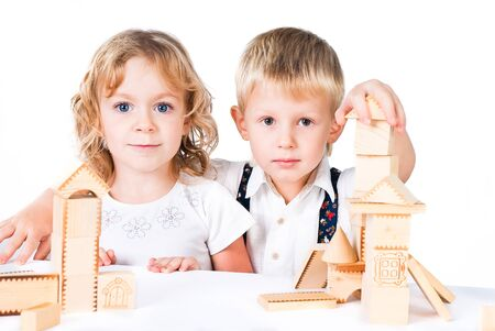 Two kids playing with wooden blocks indoor on white background