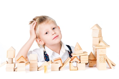displace: little boy stacks the house from wooden blocks isolated on white background