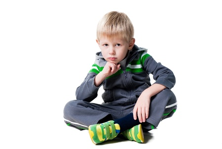 bambini pensierosi: carino ragazzo riflessivo seduto sul pavimento isolato su sfondo bianco Archivio Fotografico