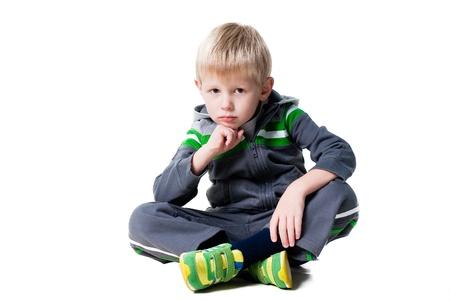 cute thoughtful boy sitting on floor isolated on white background photo