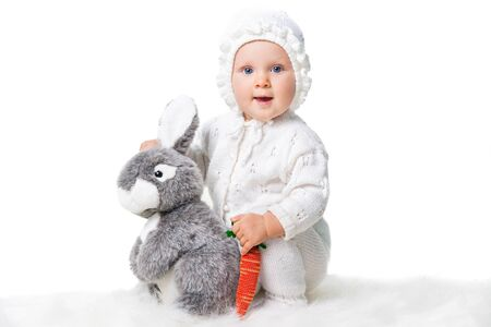 cute infant  girl playing with toy rabbit and parrot isolated on white photo