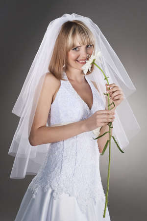 beautiful bride holding flower on studio neutral background photo