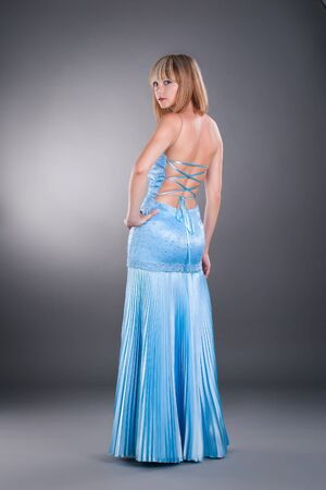 attraction young woman wearing blue gown on studio neutral background photo