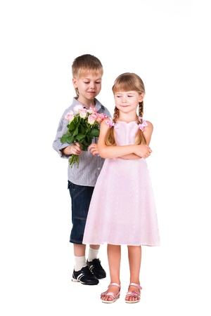 Little boy gives roses to girl isolated on white photo