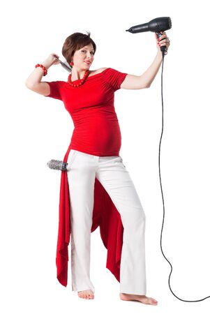 young pregnant woman styling your hair with hairdryer isolated on white background photo