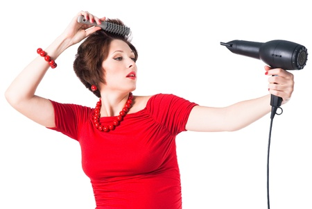 young pregnant woman styling your hair with hairdryer isolated on white background Stock Photo