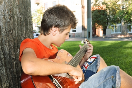 teenager boy playing guitar at park