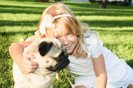 cute girl  hugging with lovely dog at the park on summer day