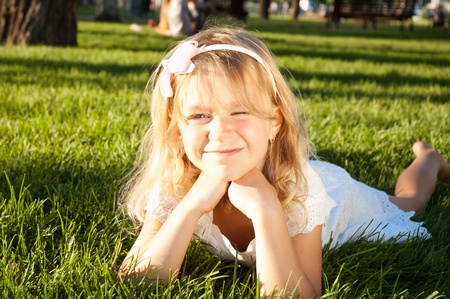 6 years old girl relaxing at the meadow on sunny day photo