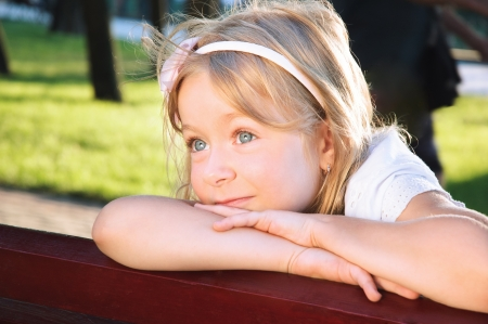 smiling little girl portrait at a park on summer shunny day Stock Photo